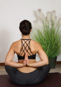 posizione yoga con mani giunte dietro alla sschiena